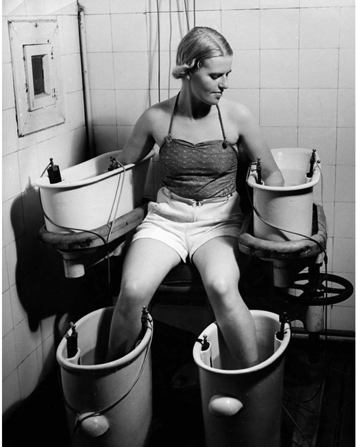 A Young Woman Holds Her Arms And Legs In Four Water Bathes With Electric Current, To Improve Blood Circulation, Circa 1938