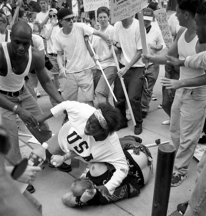 18-Year-Old Keshia Thomas Protects A Fallen Man, Believed To Be Associated With The Ku Klux Klan From An Angry Mob Of Anti-Clan Protestors. Ann Arbor, Michigan USA. 1996 By Mark Brunner