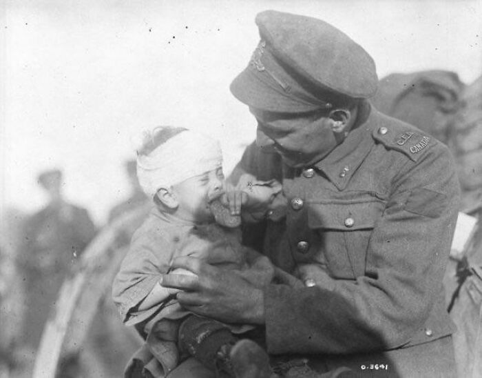 WWI. A Canadian Soldier Tries To Comfort A Little Belgian Baby, Who Was Hurt And Whose Mother Was Killed By An Artillery Shell. November 1918
